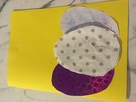 Na stoliku znajduje się żółta kartka z trzema jajkami: fioletowym, białym w szare kropki oraz blado-niebieskim