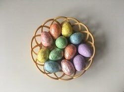 W koszyku znajdują się pisanki w kolorach: żółtym, zielonym, niebieskim, fioletowym, pomarańczowym i różowym