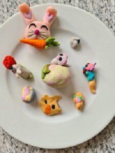 Na talerzu znajdują się ulepione z plasteliny postaci zajączka, kurczaczka i innych