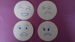 Na fioletowym tle znajdują się cztery kółka z narysowanymi emocjami: radością, smutkiem, strachem i złością