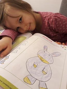 Dziewczynka kładzie głowę na książkę. Na ilustracji znajduję się zajączek