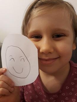 Dziewczynka jest uśmiechnięta i trzyma w ręku kółko z narysowaną emocją - radość
