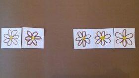 Na brązowym tle znajduję się pięć narysowanych kwiatków.