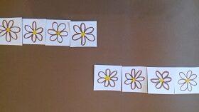 Na brązowym tle znajduję się osiem narysowanych kwiatków.