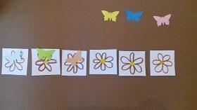 Na brązowym tle znajduję się sześć narysowanych kwiatków, na trzech z nich leżą motyle. Trzy motyle znajdują się powyżej trzech kwiatków.