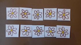Na brązowym tle znajduję się dziesięć narysowanych kwiatków.