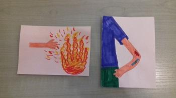 Na stole znajdują się dwie ilustracje. Na jednej narysowany jest ogień i ręka, na drugiej postać z ręką.