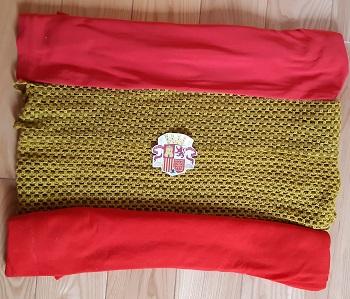 Flaga Hiszpanii wykonana ze sznurka i czerwonych materiałów. Na środku leży godło