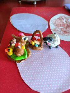 Na stole znajdują się ulepione z plasteliny postaci baranka, kurczaczka, koszyczek i inne