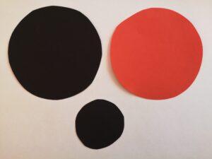 na stole leżą trzy papierowe koła. Duże czarne i czerwone. Małe czarne