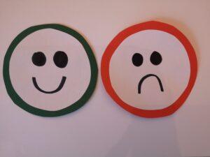 dwie narysowane buzie na papierze: smutna i wesoła