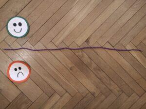 na podłodze leżą dwie papierowe buzie, smutna i wesoła oraz sznurek