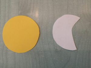 na stole leży wycięte żółte koło oraz sylweta księżyca