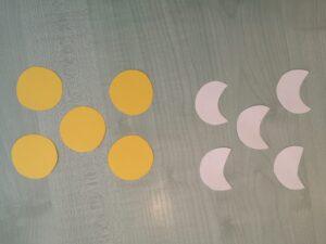 nas tole leży pięć żółtych kół i pięć białych sylwet księżyca