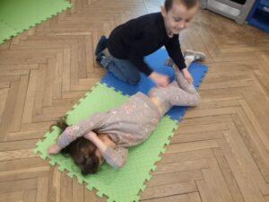 dziecko na macie układa koleżankę z pozycji bocznej uutalonej