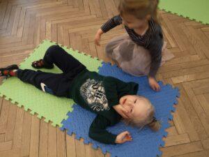 dziecko na macie układa kolegę z pozycji bocznej ustalonej
