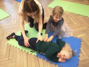 pani i dziewczynka układają chłopca w pozycji bocznej ustalonej