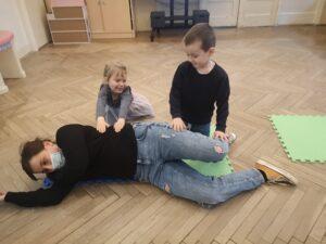 dwoje dzieci próbuje ułożyć panią w pozycji bocznej sutalonej