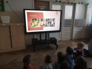 dzieci siedzą i oglądają prezentację