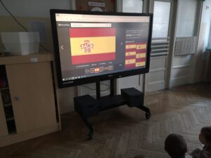 dzieci siedzą i oglądają prezentację o Hiszpanii