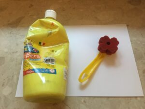 na kartce leży butelka żółtej farby i gąbka