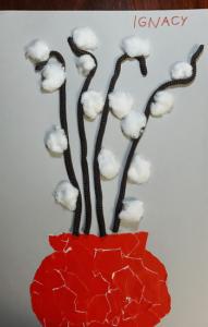 Na kartce A4 znajduję się czerwony wazon z baziami zrobionymi z brązowego sznurka oraz kulek z waty.