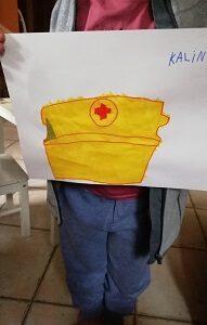 W rękach dziecka znajduję się kartka A4 z narysowaną żółtą apteczką