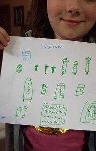 W rękach dziecka znajduję się kartka A4 z narysowanymi przedmiotami higienicznymi