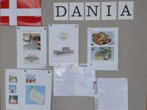 Na tablicy umieszczony jest napis DANIA, po lewej stronie widać flagę Danii – czerwony prostokąt z białym krzyżem. Zawieszone są kartki ze zdjęciami mebli, potraw oraz ciekawostek o Danii.