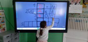Na tablicy multimedialnej narysowana jest krzyżówka, dziewczynka wpisuje trzecie hasło – NOC.