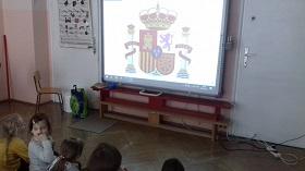 Dzieci siedzą na podłodze, zwrócone twarzami do tablicy multimedialnej. Na tablicy znajduję się godło Hiszpanii.