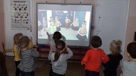 Dzieci stoją przed tablicą multimedialną, na której widać dzieci, które tańczą.