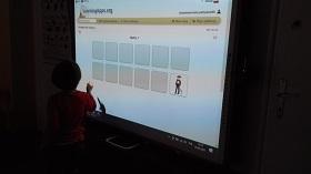 Przy tablicy multimedialnej stoi chłopiec, trzyma w ręku długopis. Na tablicy znajdują się szare kafelki.