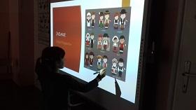Przy tablicy multimedialnej stoi dziewczynka, trzyma w ręku długopis. Na tablicy znajduję się grafika z postaciami w strojach ludowych.
