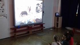 Dzieci siedzą na podłodze, zwrócone twarzami do tablicy multimedialnej. Na tablicy wyświetlany jest film o corridzie.
