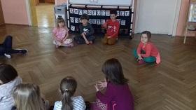 Dzieci siedzą na podłodze w siadzie skrzyżnym.