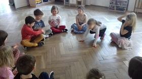 Dzieci siedzą w siadzie skrzyżnym w kółeczku i podają sobie małą piłkę