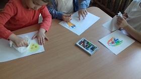 Dzieci siedzą przy stole i rysują pastelami po białych kartkach. Jedna dziewczynka rozciera pastele chusteczką.