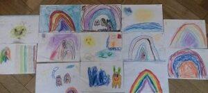 Prace plastyczne dzieci wykonane pastelami. Znajdują się na podłodze.
