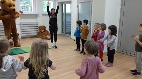 Dzieci stoją na podłodze, zwrócone są w kierunku Pani, która pokazuje im ćwiczenia
