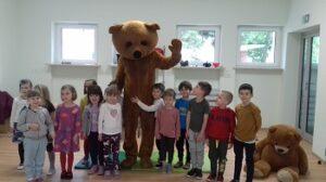 Dzieci stoją z brązowym misiem i się uśmiechają do zdjęcia