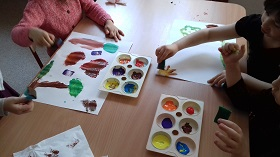 Na stole znajdują się kartki A3 oraz dwie palety farb. Dzieci trzymają w rękach gąbki, którymi malują