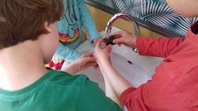 Dzieci znajdują się nad umywalką, z której leci woda. Dzieci płuczą gąbki po farbach.