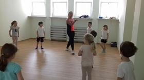 Dzieci znajdują się na sali gimnastycznej. Na środku sali stoi Pani, która wskazuje ćwiczenia dzieciom