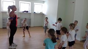 Dzieci znajdują się na sali gimnastycznej. W rękach trzymają woreczki