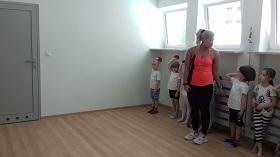 Dzieci znajdują się na sali gimnastycznej. Przygotowują się do rzutu woreczkiem