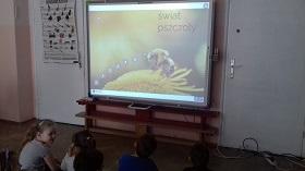 Dzieci siedzą przed tablica interaktywną. Na niej znajduję się postać pszczoły siedzącej na kwiecie. Napis: Świat pszczoły.