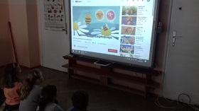 Dzieci znajdują się przed tablicą interaktywną. Na tablicy wyświetlany jest film o pszczole.