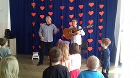 Dzieci stoją zwrócone w kierunku dwóch panów. Jeden z nich trzyma w rękach gitarę.