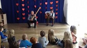 Dzieci siedzą na podłodze, zwrócone są w kierunku dwóch panów. Jeden z nich trzyma w rękach gitarę, drugi deszczownie